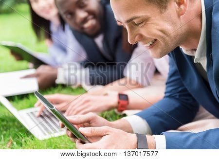 Jubilation in the air. Positive handsome delighted man smiling and using tablet while lying on the grass with his colleagues