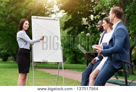 Look here. Cheerful charming smiling woman standing near board and showing graph to her colleagues while working together on the project