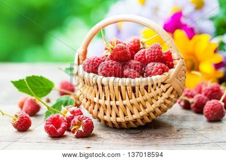 Fresh Raspberries In Basket And Flower Bouquet On On Background Outdoors