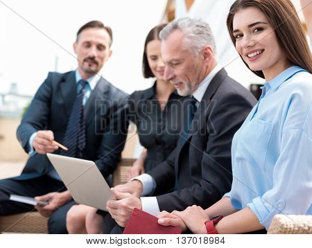 Switch on joy. Cheerful beautiful woman smiling and sitting on the settee while her colleagues using laptop in the background