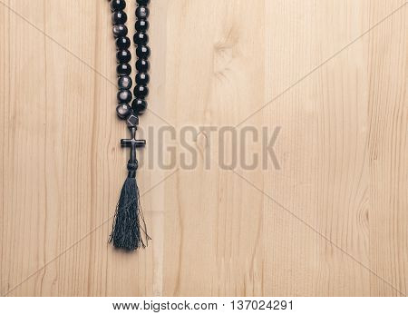 Black Stone Christianity Beads With Cross On Wooden Desk