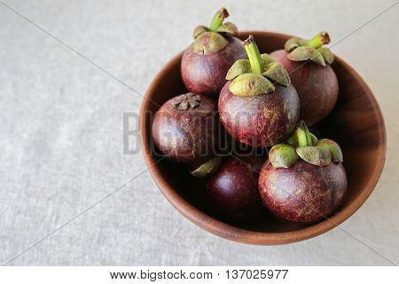 Mangosteen in wooden fruit bowl copy space background
