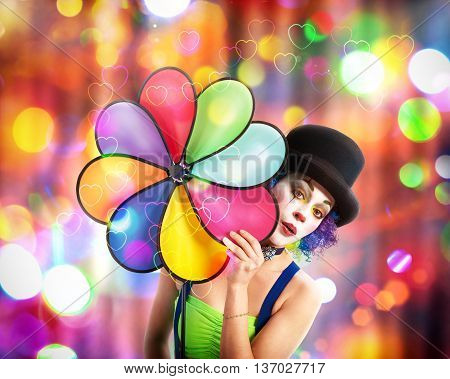 Smiling clown with hat and background with colored lights
