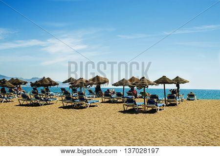 View on sunny idyllic beach with umbrellas and deckchairs against of seascape under blue sky. Malaga Spain Beach La Malagueta.