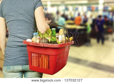 Young woman keeps shopping basket with food and drinks