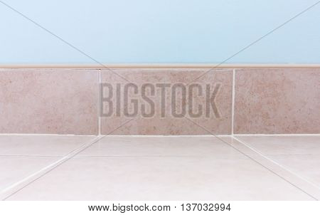 Blue concrete wall with the pink tile around the room floor.