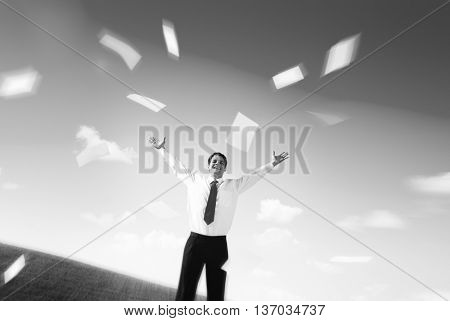 Business Man on the Field with his Arms Raised Throwing Paperworks