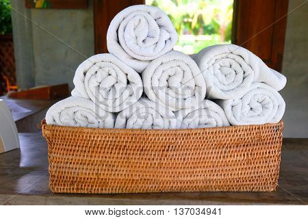 white roll towels in the basket on the table