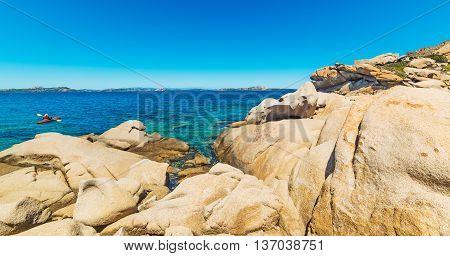 man kayaking by Sardinian rocky coastline Italy