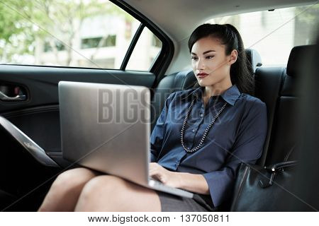 Pretty young business lady sitting on backseat of car and working