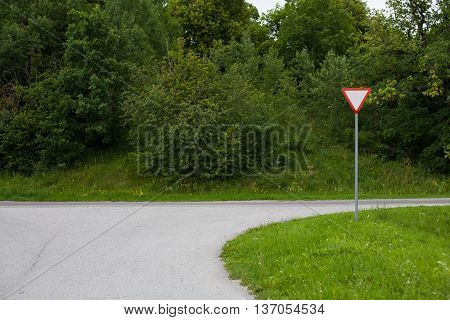 Give way traffic sign on a suburban road beside a forest