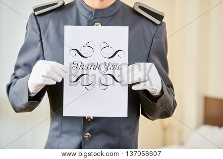 Hotel clerk holding thank you sign in a hotel room
