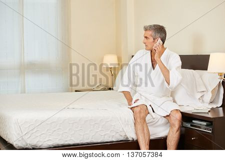 Elderly man making a phone call in his hotel room with his smartphone