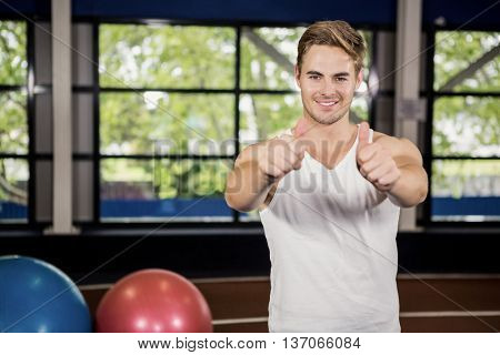 Handsome man showing his thumbs up at gym
