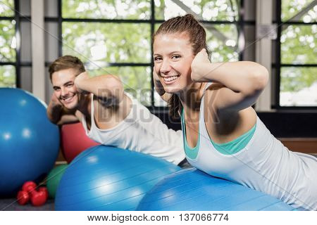 Man and woman working out on a fitness ball at gym