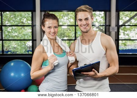 Portrait of woman standing with trainer at gym