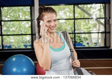 Woman with a gym bag talking on the phone at gym