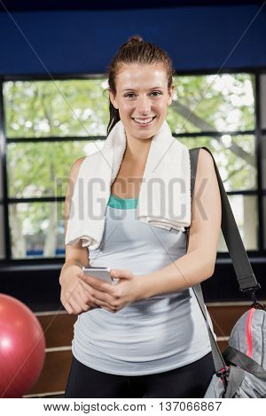 Portrait of woman with a gym bag using her phone at gym