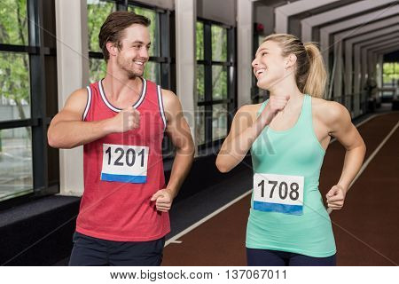 Happy man and woman running together at gym