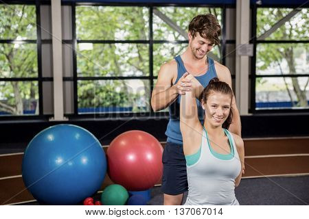 Trainer assisting woman with stretching exercise at gym