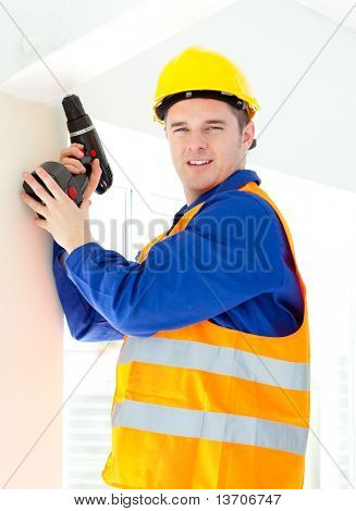 Attractive young worker holding a tool standing on a ladder in a house