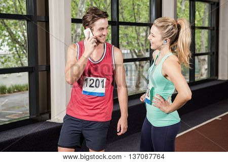 Man and woman listening to music and talking to the phone at gym