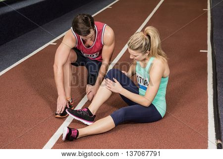 Man assisting an injured woman on the running track at gym