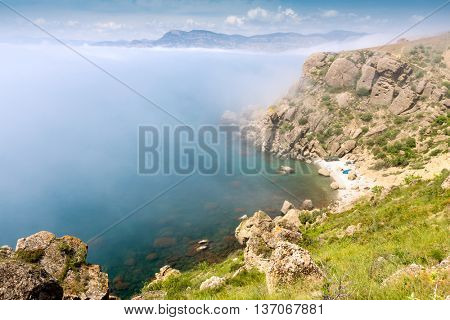 summer scene with foggy rocks over sea