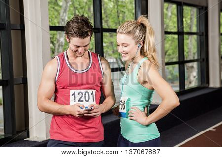 Man and woman listening to music and using phone at gym