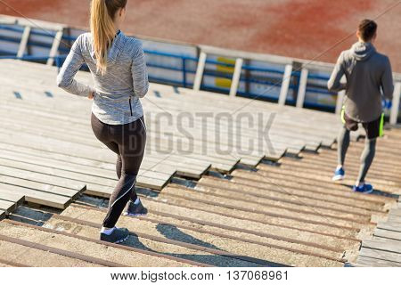 fitness, sport, exercising and lifestyle concept - close up of couple running downstairs on stadium