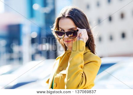 summer, leisure, vacation and people concept - smiling young woman with sunglasses in city