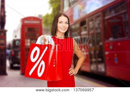 sale, discount, tourism and holidays concept - smiling young woman in red dress with shopping bags with percent sign over london city street background