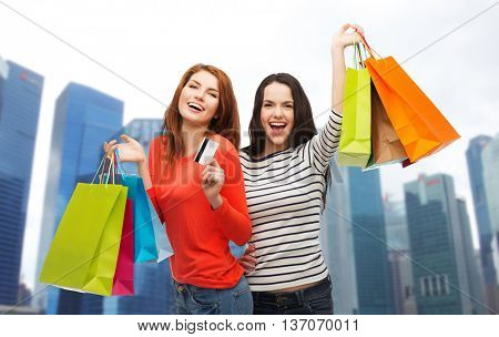 shopping, sale, tourism and people concept - two smiling teenage girls with shopping bags and credit card over singapore city skyscrapers background