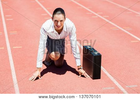 Portrait of happy businesswoman with briefcase in ready to run position on running track