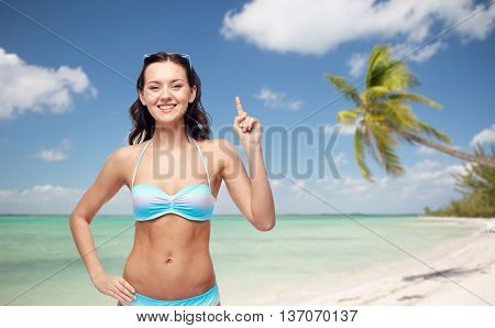people, travel, tourism, swimwear and summer holidays concept - happy young woman in bikini swimsuit pointing finger up to something imaginary over exotic tropical beach with palm trees background