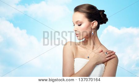 beauty, jewelry, people and luxury concept - beautiful asian woman or bride with earring, finger ring and pendant over blue sky and clouds background