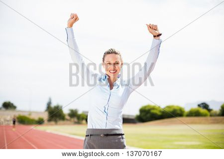 Excited businesswoman standing on the running track with hands raised