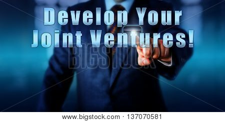 Manager is pressing the phrase Develop Your Joint Ventures! on a control screen. Business objective concept call to action and motivational metaphor. Close up of male torso in blue suit.