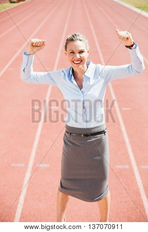 Portrait of excited businesswoman standing on the running track with hands raised