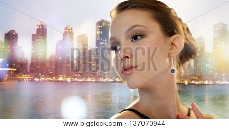 beauty, jewelry, people and luxury concept - face of beautiful young asian woman with earring over dubai city night lights background