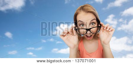 vision, education and people concept - happy smiling young woman or teenage girl eyeglasses over blue sky and clouds background