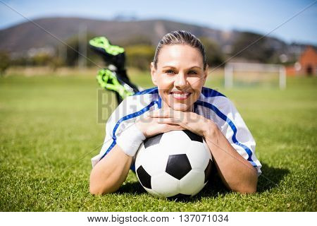 Portrait of happy female football player lying on football field with ball