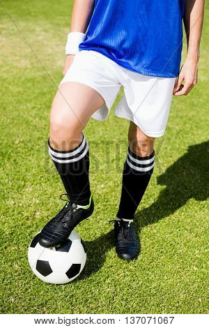 Female football player standing with her feet on ball in stadium