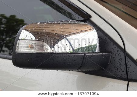 Wing mirror of white car with raindrops.