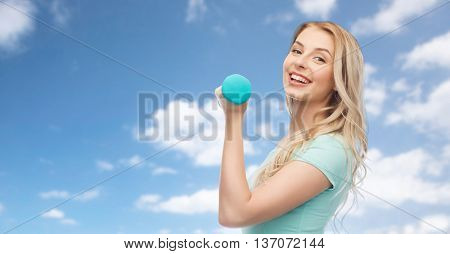 fitness, sport, exercising and people concept - smiling beautiful sporty woman with dumbbell over blue sky and clouds background