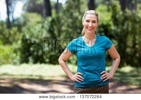 Woman smiling and posing with hands on hips on the wood