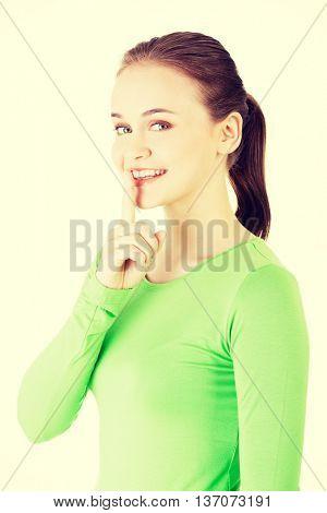 Teen girl with finger on her lips.
