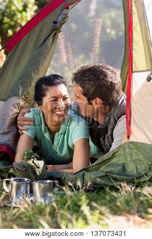 Couple laying and holding each other on a tent