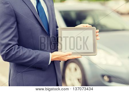 transport, business trip, technology and people concept - close up of young man showing tablet pc computer blank screen and car outdoors
