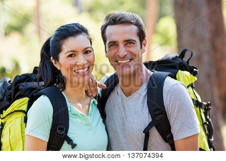 Couple smiling and posing with backpacks on the wood